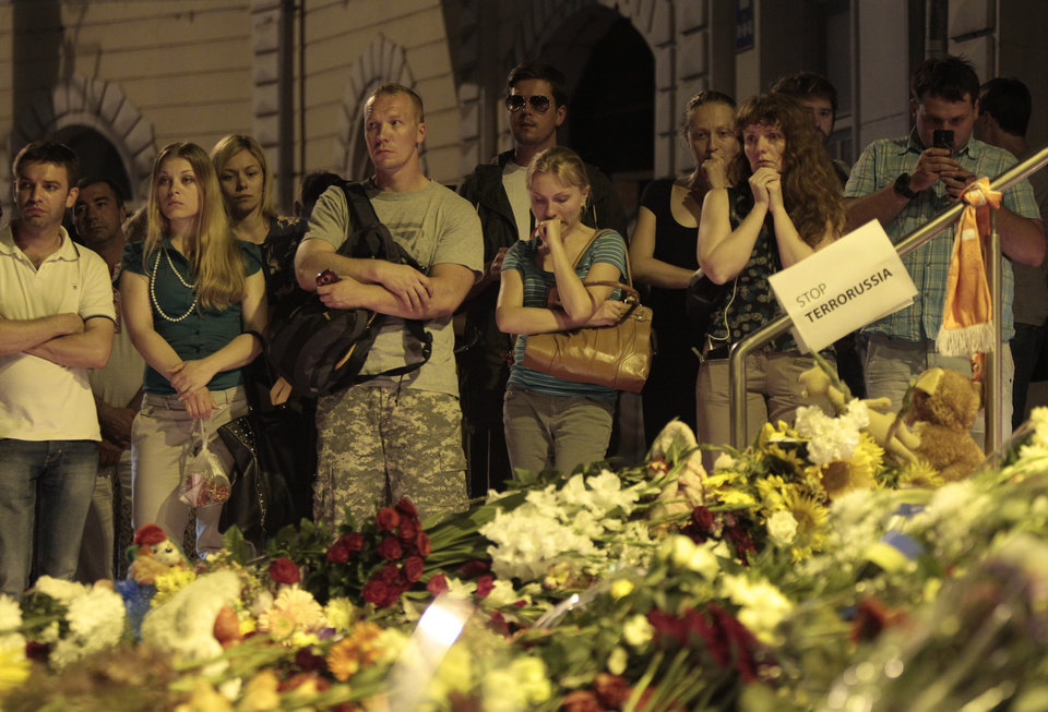 Photo - People stand near flower tributes placed outside the Dutch embassy to commemorate victims of Malaysia Airlines plane crash in Kiev, Ukraine, Thursday, July 17, 2014.  A Malaysian Airlines passenger jet was shot down in eastern Ukraine on Thursday, and both the Ukrainian government and pro-Russian rebels blamed one another for the attack. (AP Photo/Sergei Chuzavkov)