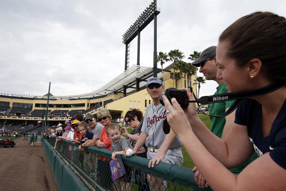 Photo - Emily Frederick, right, takes a picture of her husband, Brendt Frederick, wearing white-rimmed sunglasses, and son, Parker Frederick, 2, all from St. Clair Shores, Mich., before a spring training exhibition baseball game between the Detroit Tigers and the Atlanta Braves, Wednesday, Feb. 26, 2014, in Kissimmee, Fla. After such a long, cold season, Americans across the winter-weary Midwest and the East Coast are desperate to escape to warm-weather destinations in California, Arizona and Florida. (AP Photo/Alex Brandon)