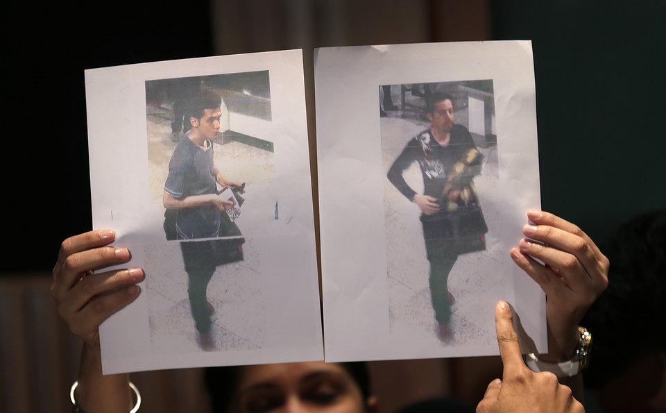 Photo - Pictures of the two men, a 19-year old Iranian, identified by Malaysian police as Pouria Nour Mohammad Mehrdad, left, and the man on the right, his identity still not released, who boarded the now missing Malaysia Airlines jet MH370 with stolen passports, is held up by a Malaysian policewoman during a press conference, Tuesday, March 11, 2014 in Sepang, Malaysia. One of the two men traveling on a missing Malaysian Airlines jetliner was an Iranian asylum seeker, officials said Tuesday, as baffled authorities expanded their search for the Boeing 777 on the opposite side of the country from where it disappeared nearly four days ago with 239 people on board.(AP Photo/Wong Maye-E)