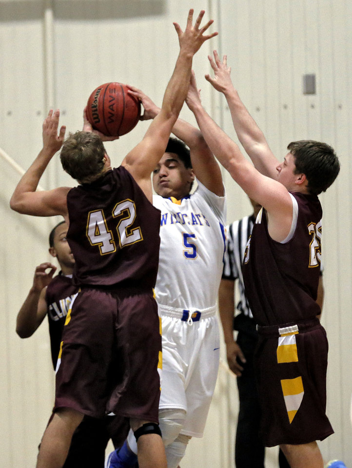 Cinton's Bowman Vowell (42) and Caden Wyer (25) defend on Piedmont's Darrius Burris (5) during a basketball tournament at the Kingfisher High School gym on Thursday, Jan. 24, 2013, in Kingfisher, Okla.  Photo by Chris Landsberger, The Oklahoman