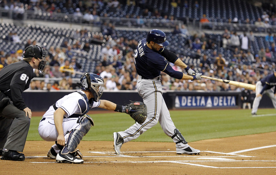 Milwaukee Brewers' Ryan Braun, right, hits a two-run home run with San Diego Padres catcher Nick Hundley, center, looking on in front of home plate umpire Clint Fagan in the first inning of a baseball game, Monday, April 22, 2013, in San Diego. (AP Photo/Alex Gallardo)