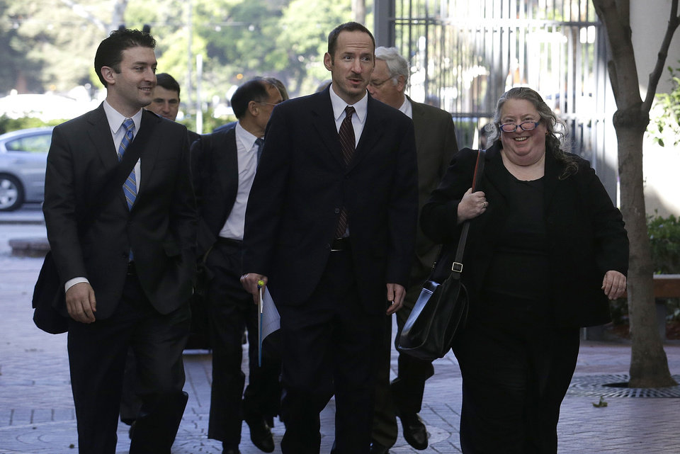 Photo - Apple attorney Rachel Krevans, right, walks with others to a federal courthouse in San Jose, Calif., Tuesday, April 29, 2014. The Silicon Valley court battle between Apple and Samsung is entering its final phase. Lawyers for both companies are expected to deliver closing arguments Tuesday before jurors are sent behind closed doors to determine a verdict in a closely watched trial over the ownership of smartphone technology. (AP Photo/Jeff Chiu)