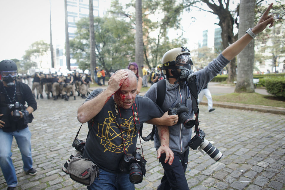 Photo - Colleagues assist Reuters photographer Sergio Moraes, center, after being injured in the head with a rock during a protest against the 2014 World Cup in Belo Horizonte, Brazil, Thursday, June, 12, 2014. Demonstrators gathered in downtown Belo Horizonte to protest against the 2014 World Cup soccer tournament. (AP Photo/Victor R. Caivano)
