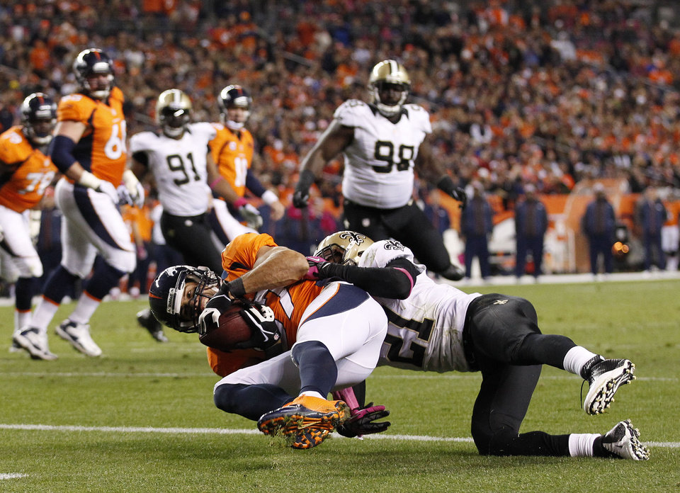 Photo -   Denver Broncos wide receiver Eric Decker (87) comes down with a pass from quarterback Peyton Manning for a touchdown against New Orleans Saints cornerback Patrick Robinson (21) in the fourth quarter of an NFL football game, Sunday, Oct. 28, 2012, in Denver. (AP Photo/David Zalubowski)