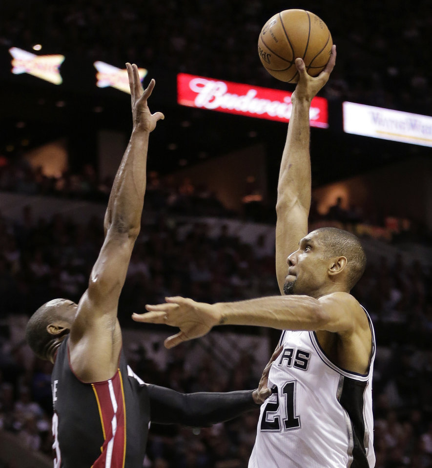 Photo - San Antonio Spurs' Tim Duncan (21) shoots as Miami Heat's Dwyane Wade defends during the first half at Game 4 of the NBA Finals basketball series, Thursday, June 13, 2013, in San Antonio. (AP Photo/Eric Gay)