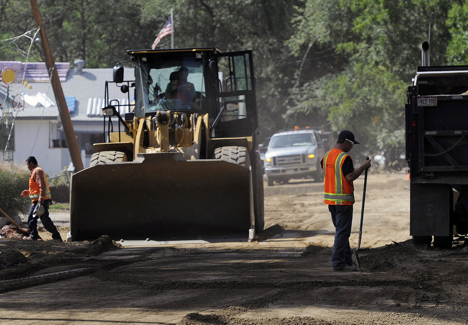 Photo - A construction crew works on repairing Park St. in Lyons, Colo., on Thursday, Sept. 19, 2013.  Local governments are starting to clear debris and repair infrastructure after last week's flooding. (AP Photo/Chris Schneider)