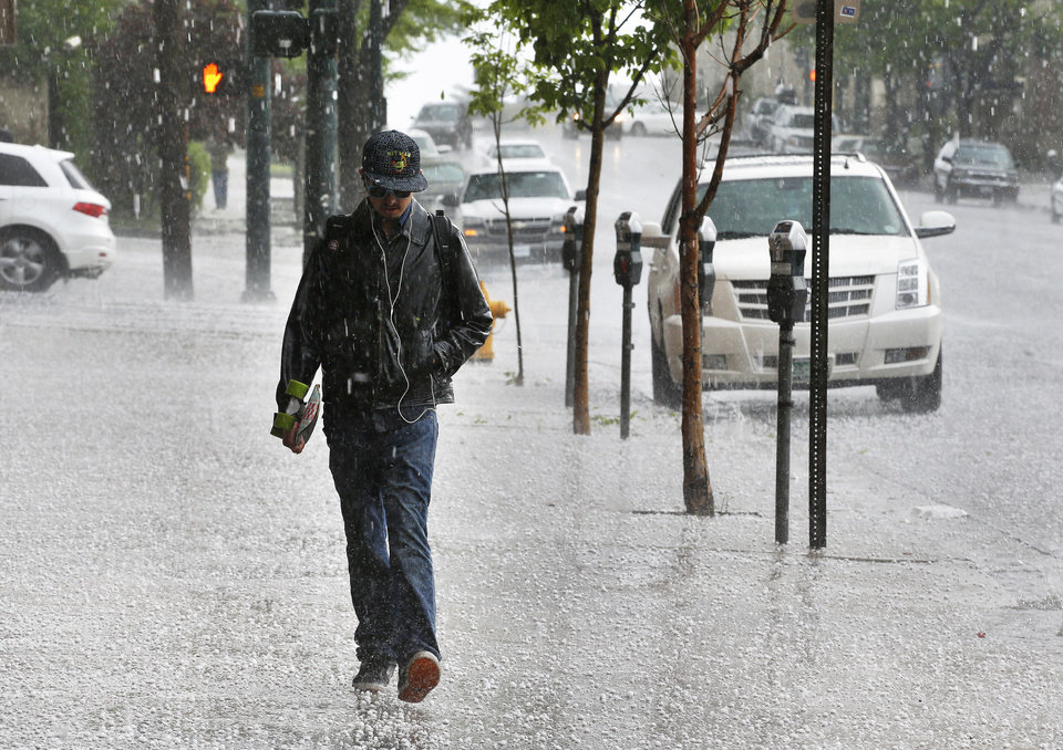 Photo - Robert Teran walks to work as a hail storm falls over downtown Denver, Thursday May 22, 2014. More spring thunderstorms began rolling into the Front Range and eastern Colorado on Thursday, a day after six tornadoes touched down east of Denver. Heavy hail was reported in Red Feather Lakes northwest of Fort Collins, and more hail is falling in Denver. (AP Photo/Brennan Linsley)