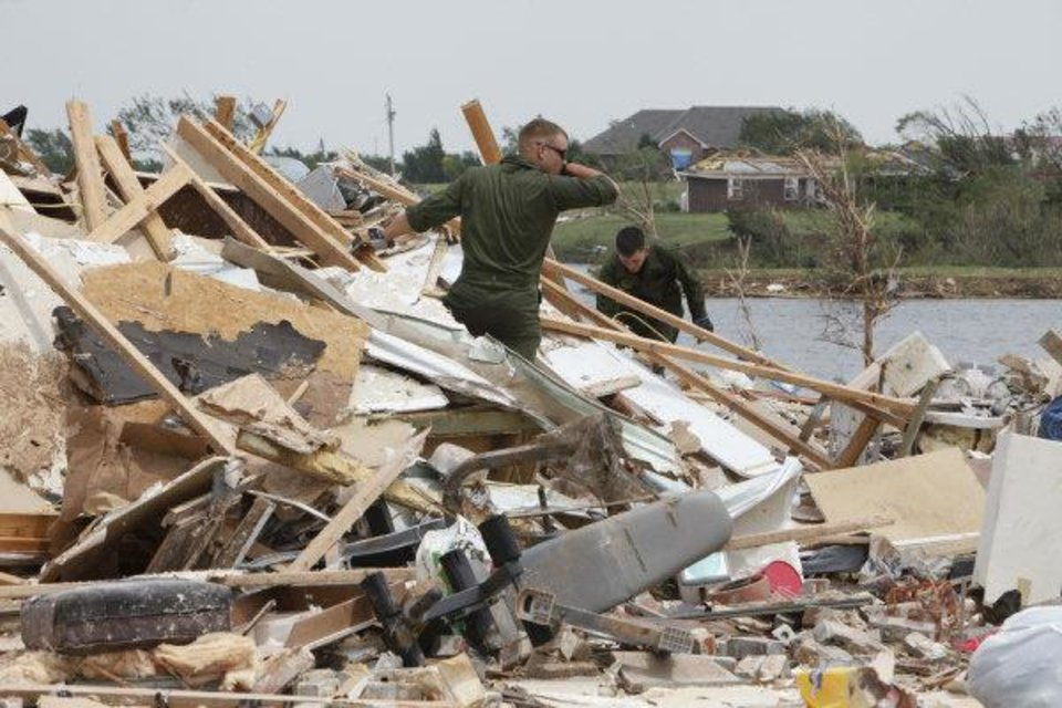 U.S. Marine Pfc. Dustin Buckner foreground, and Pfc. James Belohlavek help homeowner Kevin Roady on Falcon Lake in Piedmont on Friday. Buckner, who is from Cashion, got permission from his superiors to drive home with two friends and help those affected by the recent tornadoes. <strong>PAUL HELLSTERN</strong>