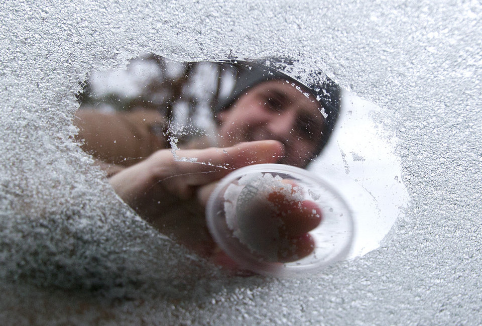 Photo - Michal Fiuk scrapes off ice from his car window Friday, Jan. 24, 2014, in Conroe, Texas. Fiuk, a native of Poland, said it was 23 below zero in his hometown Friday morning, and was stunned many business and schools in Conroe were closed or delayed.