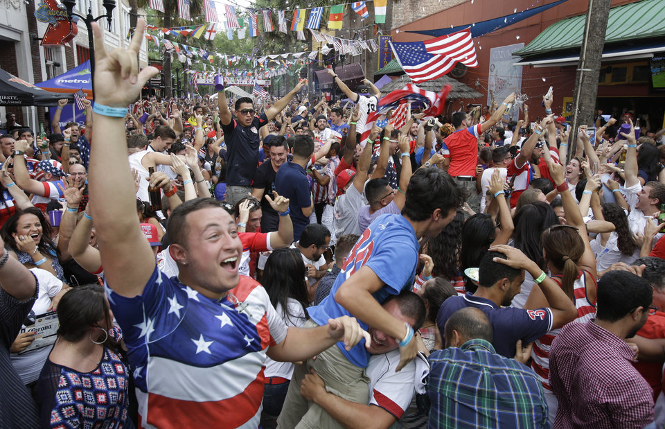 Photo - FILE - In this Sunday, June 22, 2014 file photo, fans cheer after the United States scored a goal against Portugal as they watch the World Cup soccer match on a big screen television in Orlando, Fla. The match was almost certainly the most-watched soccer game ever in the U.S., according to the Nielsen company. Viewing parties have pulled thousands of people into bars, public parks, movie theaters and other locations since the tournament began. (AP Photo/John Raoux, File)