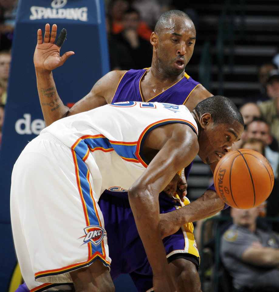 Photo - Oklahoma City's Kevin Durant (35) loses the ball as he is fouled by Kobe Bryant (24) of Los Angeles in the third quarter during the NBA basketball game between the Los Angeles Lakers and the Oklahoma City Thunder at the Ford Center in Oklahoma City, Friday, March 26, 2010. Oklahoma City won, 91-75. Photo by Nate Billings, The Oklahoman