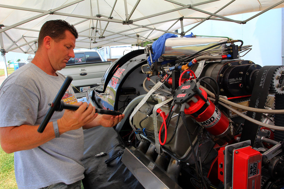 "Oklahoma City police officer Jimmy Parsons checks the spark plugs on his boat ""Domestic Disturbance II"" before the start of the Ozarka Oklahoma City Nationals Drag Boat races on the Oklahoma river Sunday, June 10th, 2012. PHOTO BY HUGH SCOTT, FOR THE OKLAHOMAN"