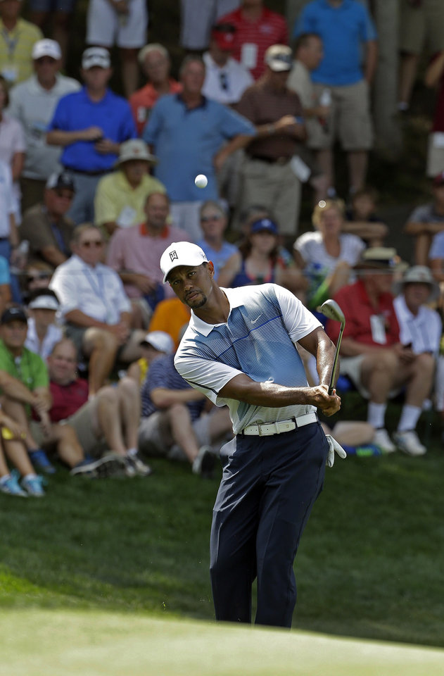 Photo - Tiger Woods hits a chip on the sixth hole during a practice round for the PGA Championship golf tournament at Valhalla Golf Club on Wednesday, Aug. 6, 2014, in Louisville, Ky. The tournament is set to begin on Thursday. (AP Photo/David J. Phillip)