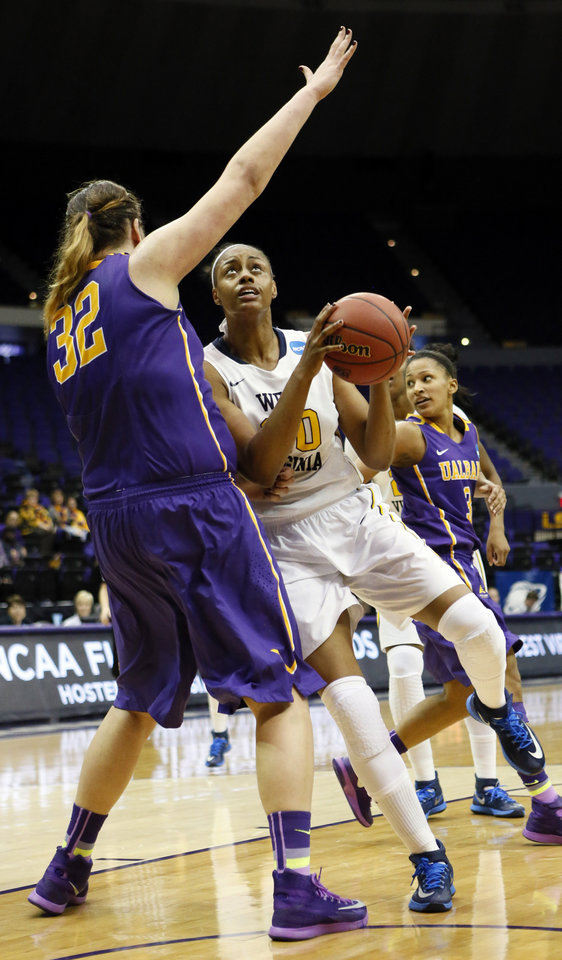 Photo - West Virginia center Asya Bussie (20) tries to lean into Albany center Megan Craig (32) in the second half of an NCAA college basketball first-round tournament game on Sunday, March 23, 2014, in Baton Rouge, La. West Virginia won 76-61. (AP Photo/Rogelio V. Solis)