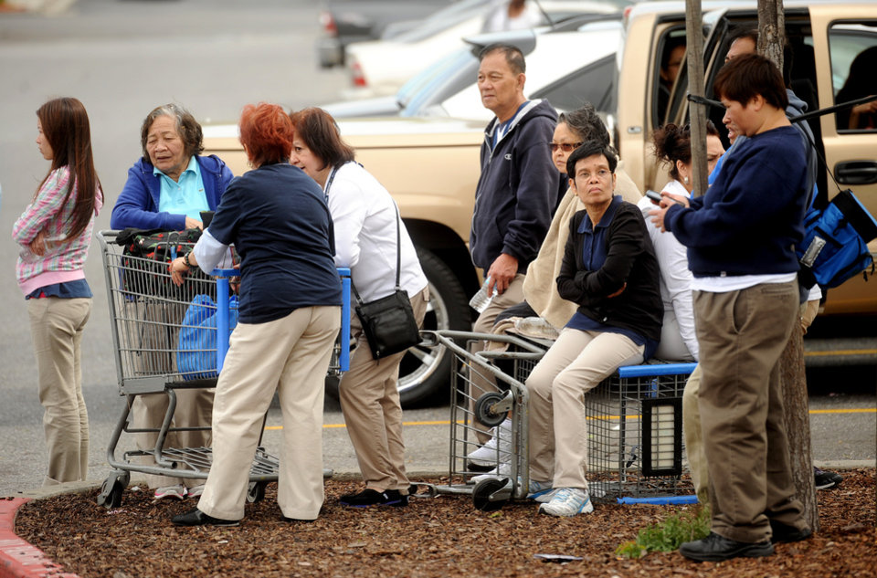 Photo - Walmart workers gather outside a Walmart in San Jose, Calif., after a motorist drove through a store entrance and began assaulting shoppers on Sunday, March 31, 2013. Four people sustained injuries during the attack according to a police spokesman. (AP Photo/Noah Berger)