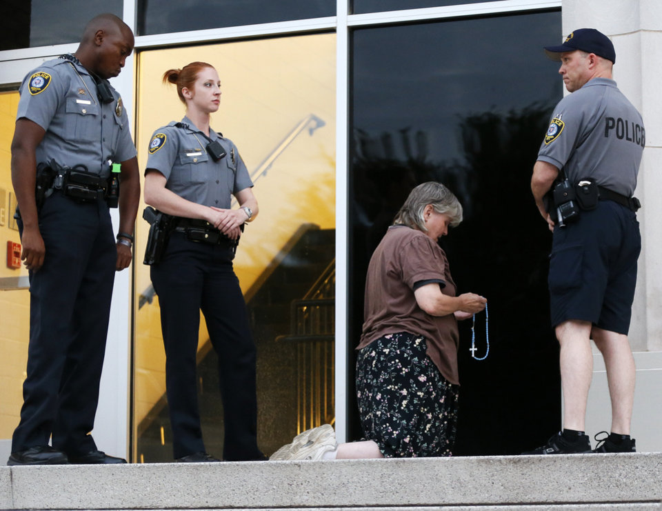 "Photo - A woman refuses to leave the entrance to the ""black mass"" on the north side of the Civic Center Music Hall during the event in Oklahoma City, Sunday, Sept. 21, 2014. Only people with tickets were allowed on the north side of the building. She was later arrested. Photo by Nate Billings, The Oklahoman"