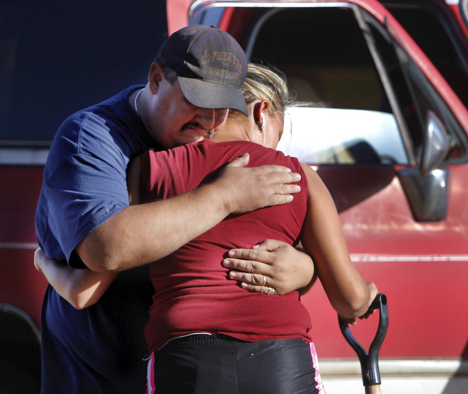 Luther firefighter Jason Winchester comforts his sister-in-law, Brandy West, as she was digging through the remains of her family's home.   West was at her property shortly after sunrise to begin searching for salvageable items, mostly documents and her mother's belongings  from inside the three bedroom frame house at 1006. S. Douglas Street. Her parents had lived in this house for 30 years before fire destroyed it.Residents  in Luther were allowed to return to the their homes early Saturday, Aug. 4, 2012, after they fled a rapidly moving wildfire yesterday that consumed at least seven structures on South Dogwood Street, leaving smoldering ashes where family homes once stood.  