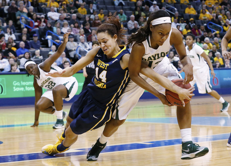 Photo - West Virginia forward Jess Harlee (14) reaches in to try and knock the ball away from Baylor forward Nina Davis (13) in the first half of an NCAA college basketball game in the finals of the Big 12 Conference women's college tournament in Oklahoma City, Monday, March 10, 2014. (AP Photo/Sue Ogrocki)