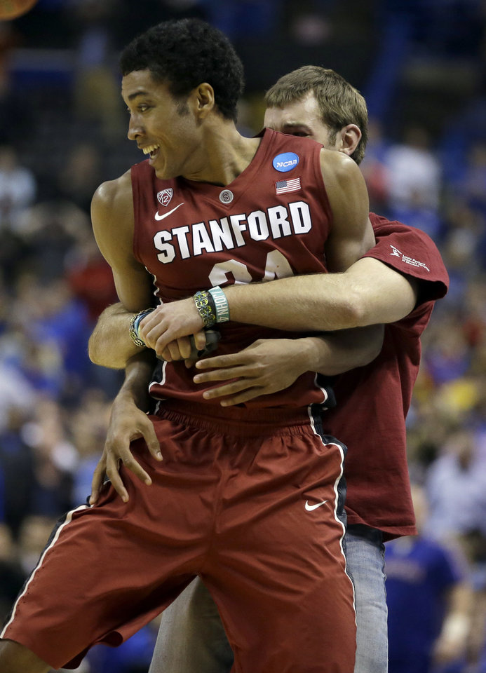 Photo - Stanford's Josh Huestis is hugged by a fan who ran on the court following Stanford's 60-57 victory over Kansas in a third-round game of the NCAA college basketball tournament Sunday, March 23, 2014, in St. Louis. (AP Photo/Jeff Roberson)