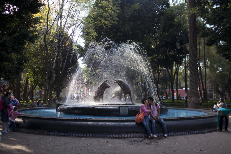 Photo -   In this photo taken on Friday, Nov. 16, 2012, people relax next to a fountain at the main square of Coyoacan, a former village south of central Mexico City.A former village south of central Mexico City, this charming neighborhood of cobblestone streets, brightly painted colonial houses and tree-shaded plazas was home to Frida Kahlo, Diego Rivera and hundreds of other artists over the decades. (AP Photo/Alexandre Meneghini)