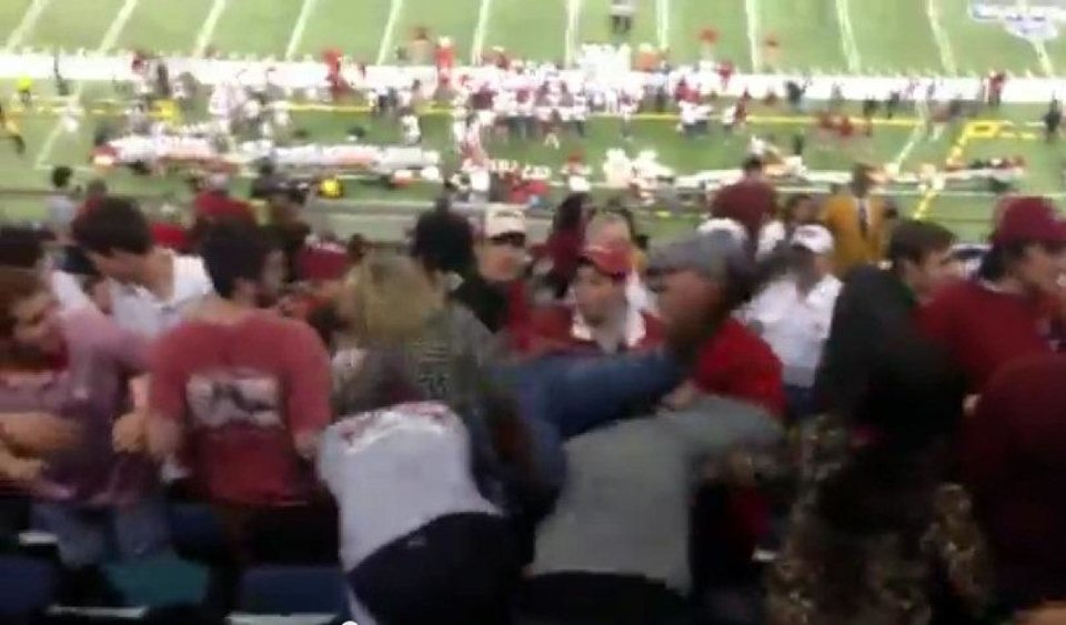 Photo - An Alabama fan, identified by yellowhammernews.com as Michelle Pritchett, dives onto a pile of OU fans during the Sugar Bowl on Thursday. PHOTO COURTESY YOUTUBE