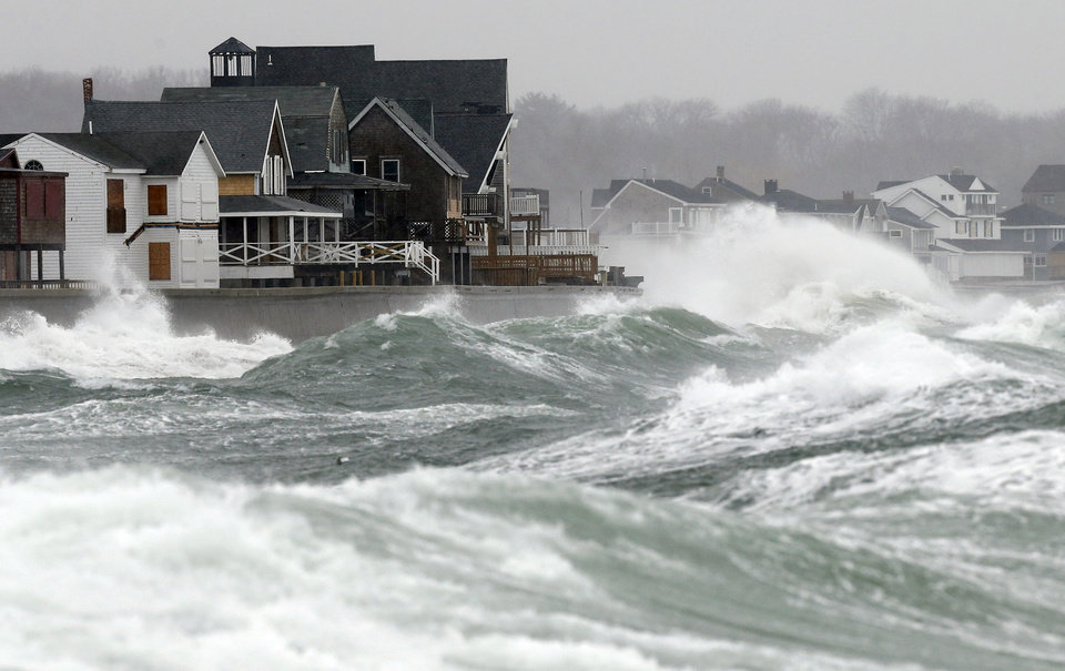 Photo - Wind-driven waves come ashore in Scituate, Mass., Wednesday, March 26, 2014. Cape Cod and the islands were expected to bear the brunt of the spring storm that struck full force Wednesday. The storm could drop up to 10 inches of snow. (AP Photo/Michael Dwyer)
