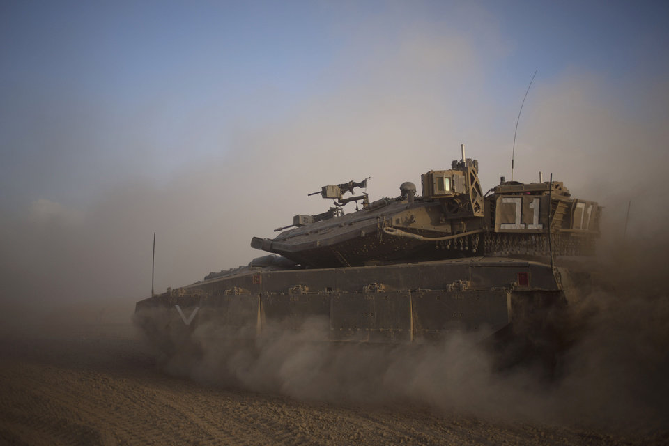 Photo - An Israeli tank maneuvers to take a position along the Israel-Gaza Border, Thursday, July 17, 2014. Israel and Hamas have begun observing a five-hour humanitarian cease-fire, as fighting extended into a 10th day. The two sides agreed to the pause following a request by the United Nations so that supplies could be delivered to Gaza.(AP Photo/Ariel Schalit)