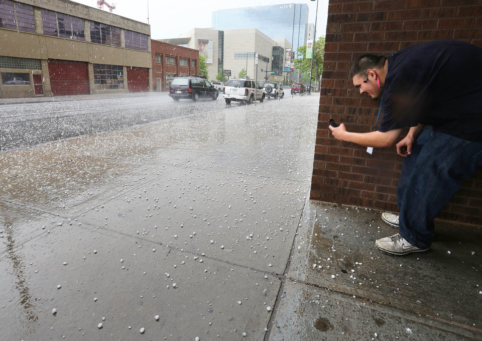 Photo - Marco Magana takes a close up phone photo of hail, as a storm cloud passes over downtown Denver, Thursday May 22, 2014. More spring thunderstorms began rolling into the Front Range and eastern Colorado on Thursday, a day after six tornadoes touched down east of Denver. Heavy hail was reported in Red Feather Lakes northwest of Fort Collins, and more hail is falling in Denver. (AP Photo/Brennan Linsley)