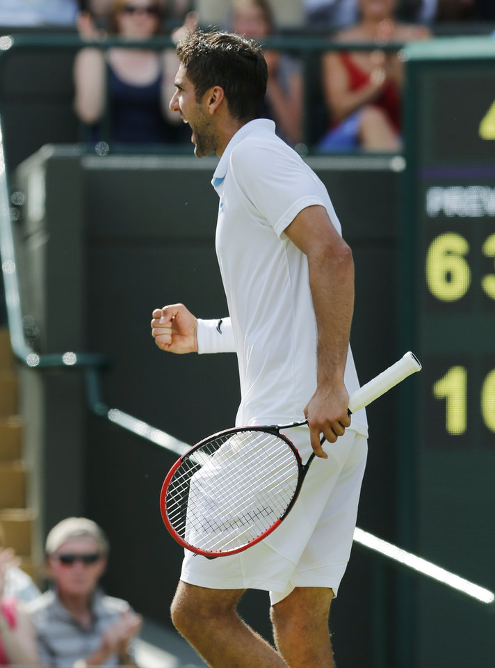 Photo - Marin Cilic of Croatia celebrates winning the third set against Novak Djokovic of Serbia during their men's singles quarterfinal match at the All England Lawn Tennis Championships in Wimbledon, London, Wednesday, July 2, 2014. (AP Photo/Ben Curtis)