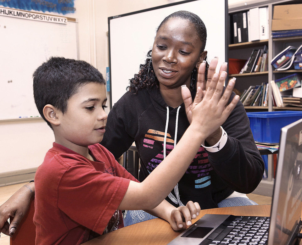 University of Central Oklahoma student Jakky Finley high-fives Linwood Elementary School third-grader Patrick Goolsby after he completed a reading lesson using a laptop computer. Photo by Jim Beckel, The Oklahoman