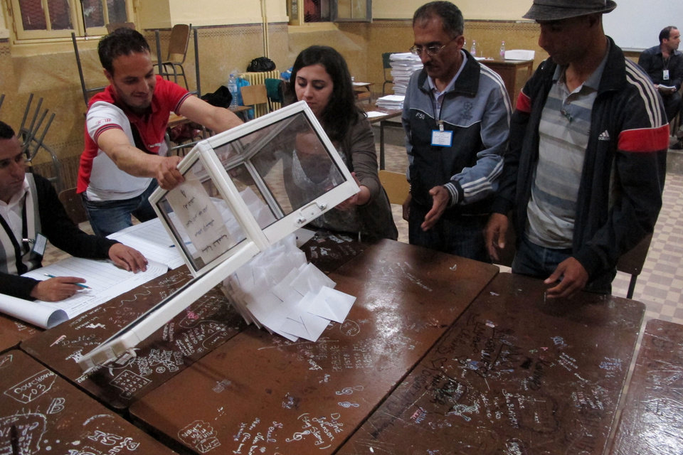 Photo -   Workers at a polling station empty ballots to begin the counting process, in the Bab el-Oued neighborhood, Algiers, Thursday, May 10, 2012. As parliamentary elections unfolded across Algeria on Thursday, voting was light for much of day in the capital, despite these contests being billed the freest in 20 years. (AP Photo/Paul Schemm).