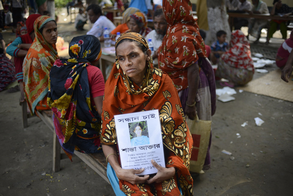 Photo - A Bangladeshi woman holds a portrait of her missing daughter at a makeshift morgue in Savar, near Dhaka, Thursday, May 9, 2013. The death toll from the collapse of a garment factory building passed 900 on Thursday even as a fire in an 11-story garment factory Wednesday night in Dhaka killed eight people, including a ruling-party politician and a top official in the country's powerful clothing manufacturers' trade group. (AP Photo/Ismail Ferdous)