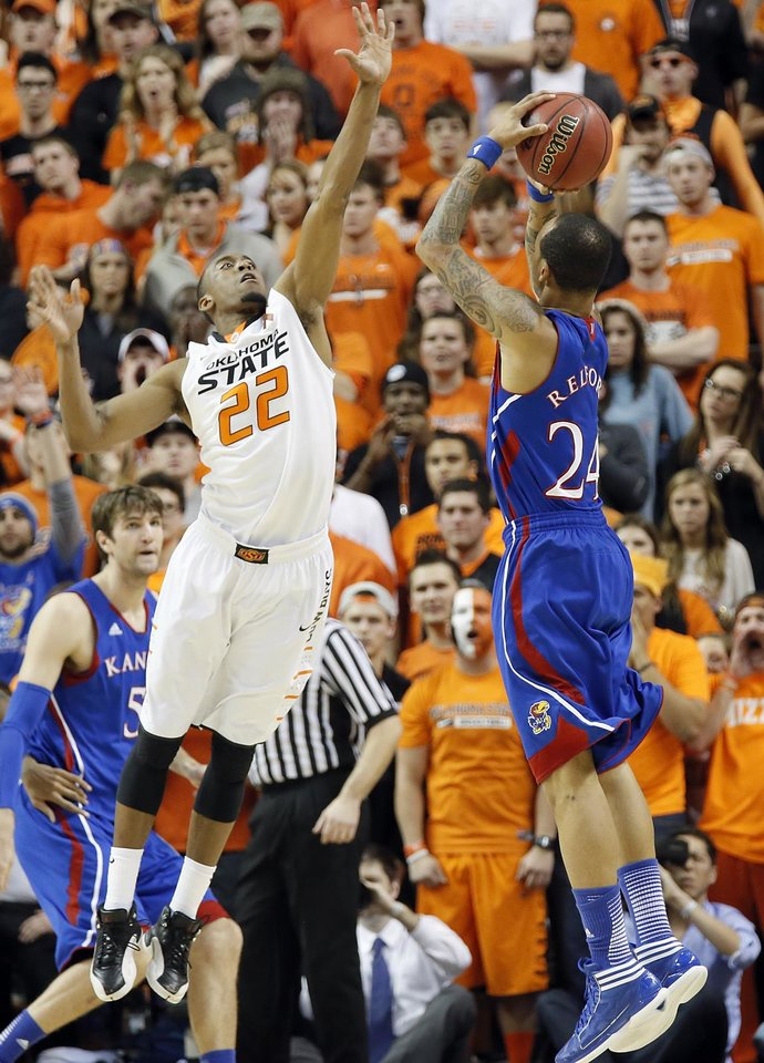 Photo - Oklahoma State 's Markel Brown (22) defends on Kansas' Travis Releford (24) during the college basketball game between the Oklahoma State University Cowboys (OSU) and the University of Kanas Jayhawks (KU) at Gallagher-Iba Arena on Wednesday, Feb. 20, 2013, in Stillwater, Okla. Photo by Chris Landsberger, The Oklahoman