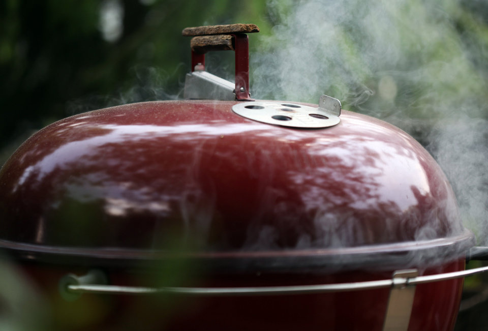 Baby back ribs are smoking inside this Weber grill, May 21, 2012, in Grosse Ile, Michigan. (Susan Tusa/Detroit Free Press/MCT)