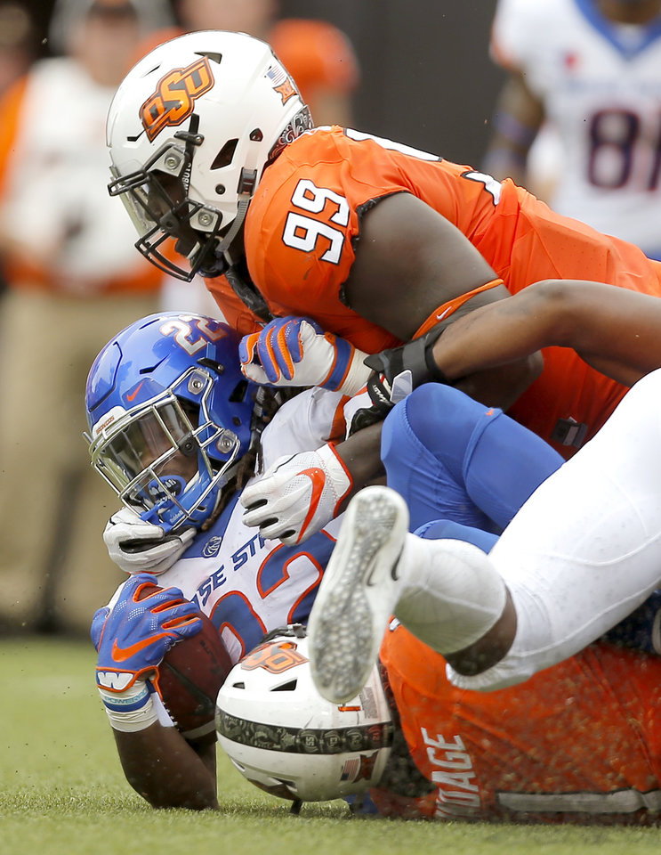 Photo - Oklahoma State's Trey Carter (99) brings down Boise State's Alexander Mattison (22) during a college football game between the Oklahoma State University Cowboys (OSU) and the Boise State Broncos at Boone Pickens Stadium in Stillwater, Okla., Saturday, Sept. 15, 2018. Oklahoma State won 44-21. Photo by Bryan Terry, The Oklahoman