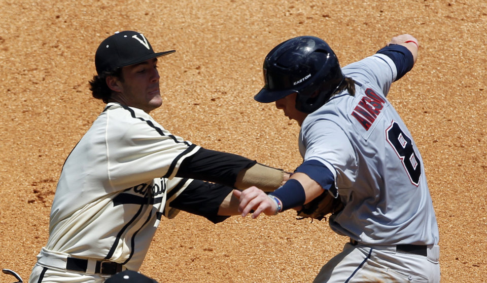 Photo - Vanderbilt's Dansby Swanson (7) tags out Mississippi's Austin Anderson (8) in a run down during the seventh inning at the Southeastern Conference NCAA college baseball tournament on Thursday, May 22, 2014, in Hoover, Ala. (AP Photo/Butch Dill)