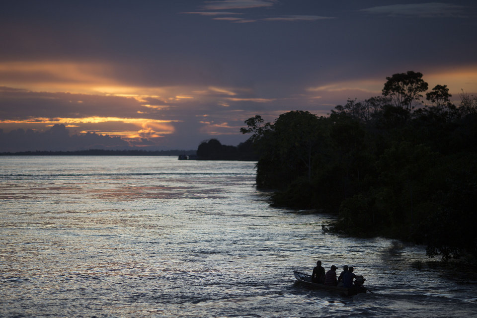 Photo - In this May 22, 2014, photo, a small boat navigates on the Solimoes river near Manaus, Brazil. While most tourists opt for speedboats for their jungle journeys, a riverboat day trip can give even Cup visitors on a tight schedule a taste of authentic Amazonian life. (AP Photo/Felipe Dana)