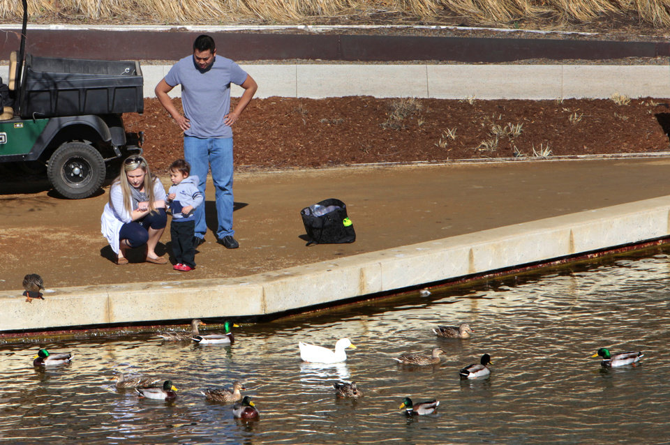 Photo -      Christina and Panumat Shontz and their son Carter, 2, feed the ducks at the Myriad Botanical Gardens on Monday in downtown Oklahoma City. Photo by David McDaniel, The Oklahoman   David McDaniel -