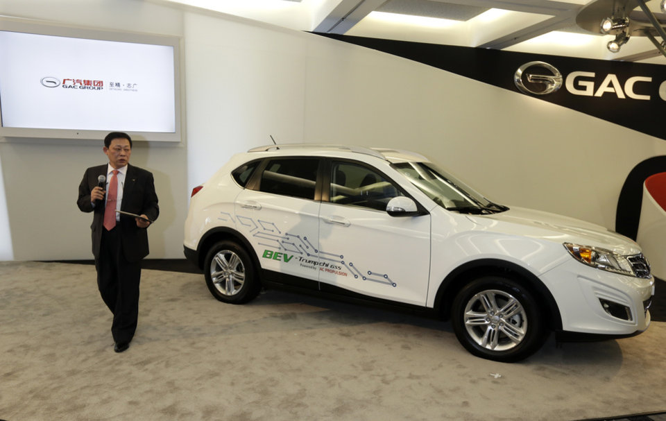 Guangzhou Automobile Group Vice President Xiangdong Huang, stands next to the automaker\'s Trumpchi GS5 concept, a pure electric vehicle, during the North American International Auto Show in Detroit, Tuesday, Jan. 15, 2013. (AP Photo/Carlos Osorio)