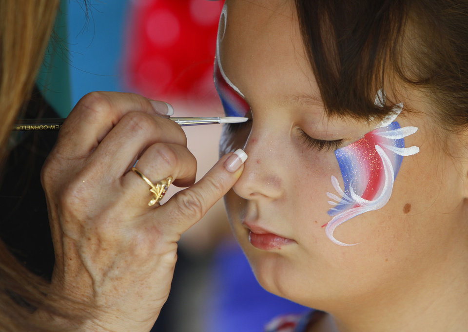 Katelyn Holstein,11, has her face painted by Lisa Powers during Celebration In The Heartland at Buck Thomas Park in Moore, Wednesday July 4, 2013. Photo By Steve Gooch, The Oklahoman
