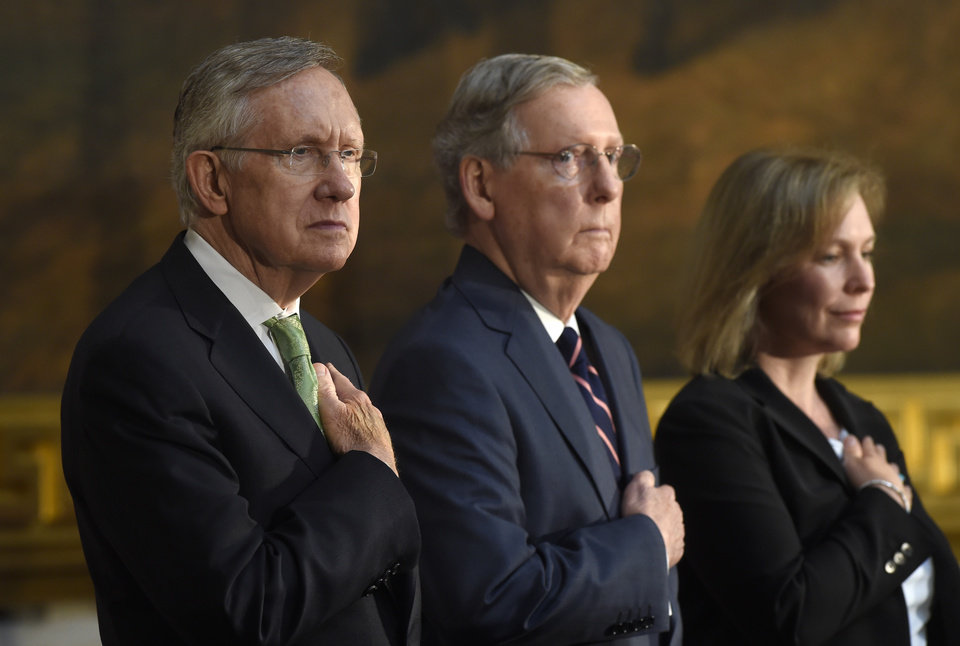 Photo - FILE - This July 9, 2014, file photo shows, from left, Senate Majority Leader Harry Reid of Nev., Senate Minority Leader Mitch McConnell of Ky., and Sen. Kirsten Gillibrand, D-N.Y., as they listen to the National Anthem during a ceremony on Capitol Hill in Washington. The Senate voted to advance an election-year bill limiting tax breaks for U.S. companies that move operations overseas. But big hurdles remain. (AP Photo/Susan Walsh, File)