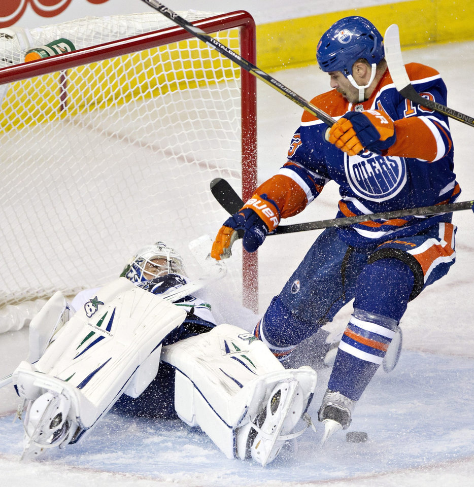 Vancouver Canucks goalie Eddie Lack, left, makes the save on Edmonton Oilers' Mike Brown during first-period preseason NHL hockey game action in Edmonton, Alberta, Saturday, Sept. 21, 2013. (AP Photo/The Canadian Press, Jason Franson)
