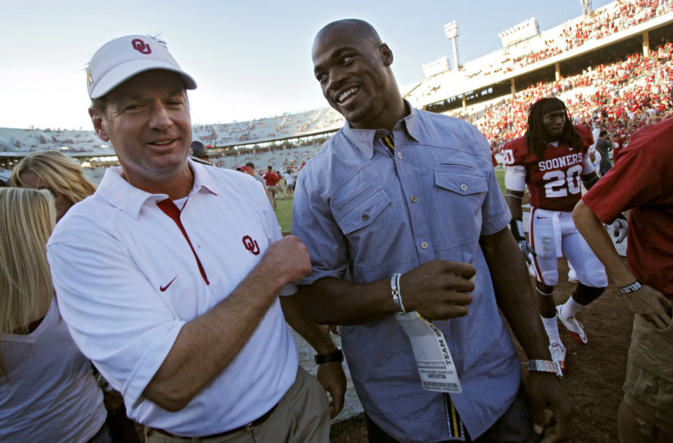 Photo - Oklahoma coach Bob Stoops walks off the field with former Sooner Adrian Peterson after the Sooners' 28-20 win over Texas in the Red River Rivalry college football game between the University of Oklahoma Sooners (OU) and the University of Texas Longhorns (UT) at the Cotton Bowl on Saturday, Oct. 2, 2010, in Dallas, Texas.   Photo by Chris Landsberger, The Oklahoman
