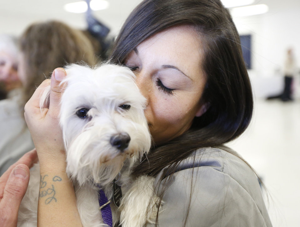 Photo - Mabel Bassett inmate Sarah Gannis makes friends with Lady, who she will train to be a companion for an elderly person.   Steve Gooch - The Oklahoman