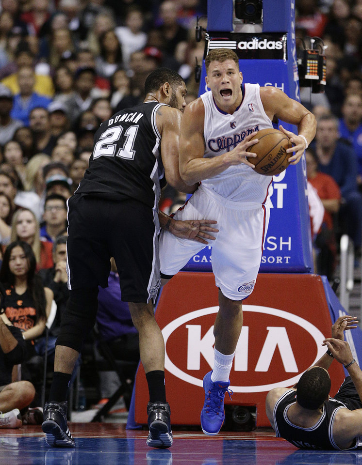 Photo - Los Angeles Clippers' Blake Griffin, right, is fouled by San Antonio Spurs' Tim Duncan during the first half of an NBA basketball game on Monday, Dec. 16, 2013, in Los Angeles. (AP Photo/Jae C. Hong)