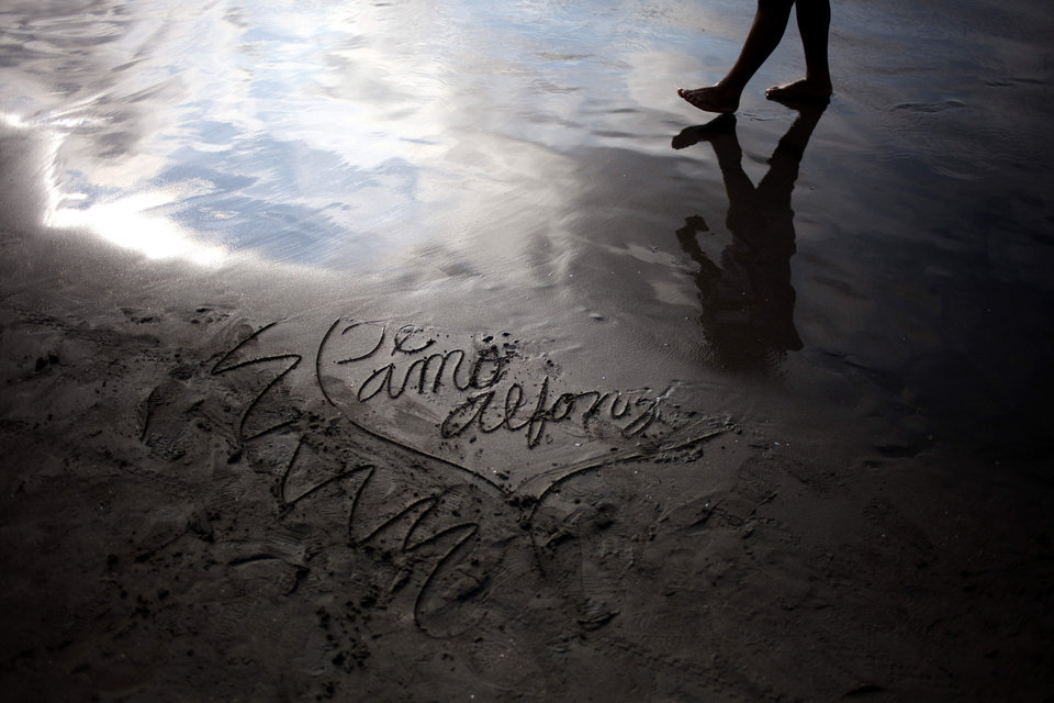 Photo - In this Jan. 18, 2013 photo, a man walks along the shoreline next to a message in the sand that reads in Spanish