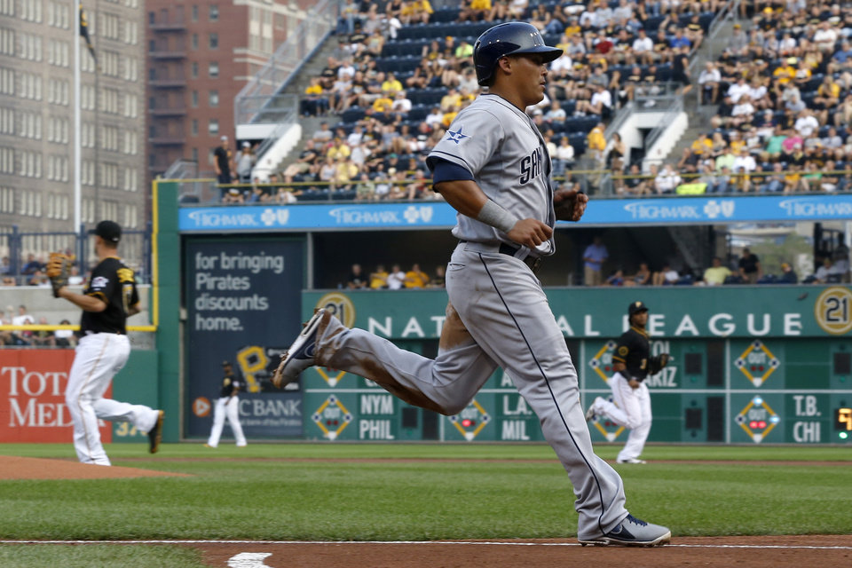 Photo - San Diego Padres' Everth Cabrera, foreground, scores on a hit by Jedd Gyorko in the first inning of a baseball game against the Pittsburgh Pirates on Saturday, Aug. 9, 2014, in Pittsburgh. (AP Photo/Keith Srakocic)