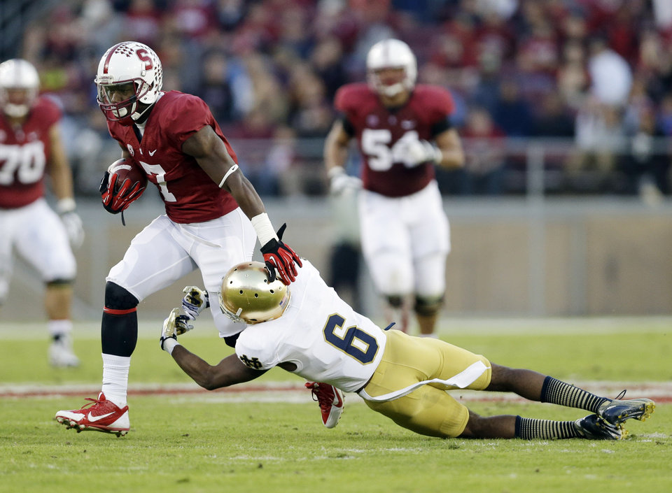 Photo - Stanford wide receiver Ty Montgomery (7) is tackled by Notre Dame cornerback KeiVarae Russell (6) after a reception during the first half of an NCAA college football game on Saturday, Nov. 30, 2013, in Stanford, Calif. (AP Photo/Marcio Jose Sanchez)