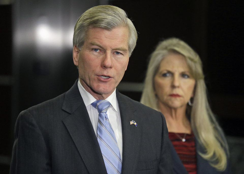 Photo - Former Virginia Gov. Bob McDonnell makes a statement as his wife, Maureen, listens during a news conference in Richmond, Va., Tuesday, Jan. 21, 2014.  McDonnell and his wife were indicted Tuesday on corruption charges after a monthslong federal investigation into gifts the Republican received from a political donor.  (AP Photo/Steve Helber)