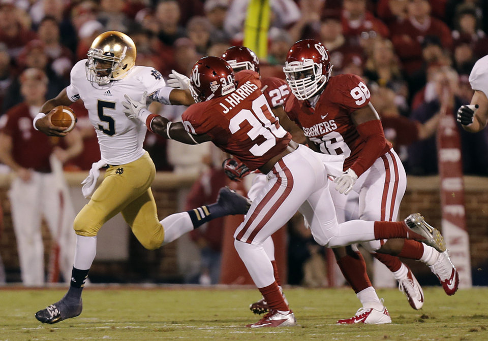 Notre Dame 's Everett Golson (5) stiff arms OU's Javon Harris (30) during the college football game between the University of Oklahoma Sooners (OU) and the Notre Dame Fighting Irish at the Gaylord Family-Oklahoma Memorial Stadium on Saturday, Oct. 27, 2012, in Norman, Okla. Photo by Chris Landsberger, The Oklahoman